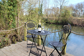 Bistro table and chairs by a stream with bottle of wine
